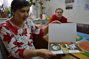 Л. И. Шатунова показывает альбом с портретами погибших воинов